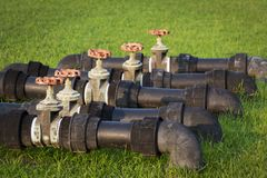 Black water pipes joined with rusty red valves for safety and clean watering system in modern building construction and industrial royalty free stock image