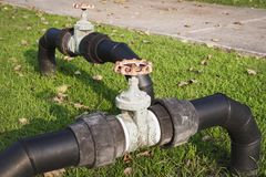 Black water pipes joined with rusty red valves for safety and clean watering system in modern building construction and industrial royalty free stock photography