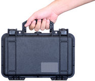 Black watertight suitcase in hand. Hand is holding a black watertight suitcase for business trip, technical service and maintenance Royalty Free Stock Image