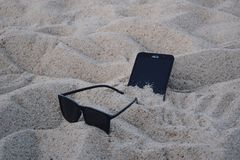 Black Wayfarer-style Sunglasses Beside Black Asus Android Smartphone on Brown Sand Stock Photos