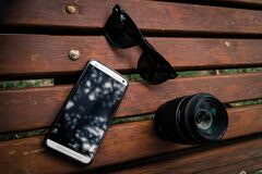 Black Wayfarer Sunglasses Near the Camera Lens Royalty Free Stock Image