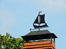 Black weather vane on home roof, Lithuania. Black metallic weather wane- sailing ship on home roof stock images