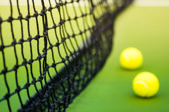 Black weaved net and two tennis balls on green hard court Stock Photos