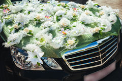 Black wedding car decorated with white roses Royalty Free Stock Photography