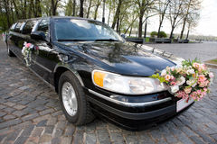 Black Wedding Limousine. Ornated with flowers Royalty Free Stock Photo
