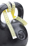 Black weight and numbers tape. The black weight of 24 kg and yellow numbers tape on a white background Royalty Free Stock Image