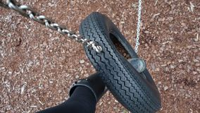 Black welly boot in a tyre swing royalty free stock image