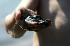 Black wet sand in child right hand Stock Images