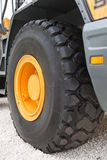 Black wheel with yellow disk of front loader Stock Images