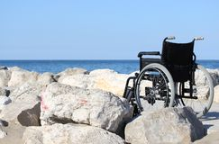 Black wheelchair on blue ocean shore in a sunny summer day Royalty Free Stock Image