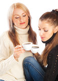 Black and white. Two lovely girls in black and white sweater having coffee Stock Image