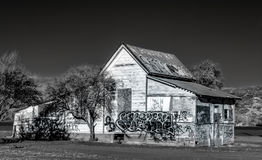 Black and White Abandoned American Farmhouse. Dilapidated and Abandoned Farm House Marked with Graffiti in the United States in Black and White Royalty Free Stock Photography