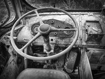 Black and white abandoned trolley car steering wheel. Closeup in woods Royalty Free Stock Photo