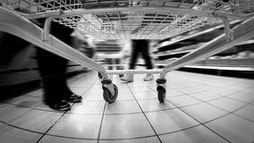 Black and white accelerated footage: trolley rolls around the supermarket stock video