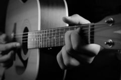 Black and white Acoustic guitar. In musician hand. Mucis proposal. Play on the guitar stock photography