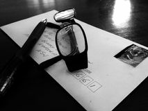 Black white addressed letter in envelope with eye glasses & pen. A black and white image of a hand written addressed envelope containing a letter to a loved Royalty Free Stock Images