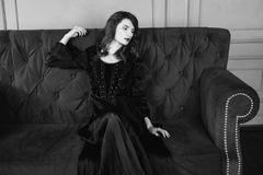 Black and white art monochrome photography. Beautiful girl with long hair and natural make-up and pale skin. A woman in a black retro dress sitting on a couch Stock Image