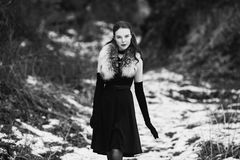 Black and white art monochrome photography. Striking girl with long hair in black clothes. A woman in a black dress and jacket. Beautiful elegant model Royalty Free Stock Photos