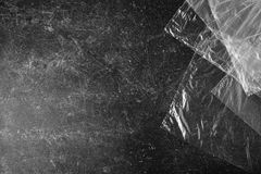 Black and white art monochrome photography. Cellophane bags on a dark marble background. Polute the nature. Eco concept Royalty Free Stock Photos