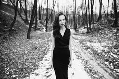 Black and white art monochrome photography. Striking girl with long hair in black clothes. A woman in a black dress and jacket. Beautiful elegant model Stock Image