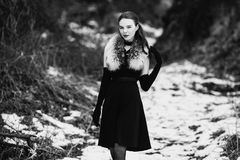 Black and white art monochrome photography. Striking girl with long hair in black clothes. A woman in a black dress and jacket. Beautiful elegant model Stock Images