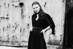Black and white art monochrome photography. Striking girl with long long hair in black clothes. A woman in a black dress and jacket. Beautiful elegant model Stock Photo