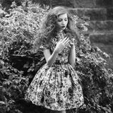 Art black and white photography. Unusual appearance. Black and white art monochrome photography. A woman with curly hair in a floral dress on a background of a Stock Photo