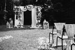 Creative black and white photography. Black and white art photography monochrome, beautiful wedding ceremony outdoors. Wedding arch made of cloth and white Royalty Free Stock Photography