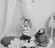 Black and white, baby boy sitting under the curtain, playing in the plane Royalty Free Stock Images