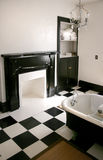 Black and white bathroom with tub. Black and white bathroom with claw foot tub, fireplace and chandelier Stock Photos