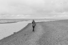 Black and white, on the beach on a cloudy day walks an attractiv Royalty Free Stock Photo