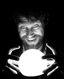 Black and white, bearded man in the dark, holding in front of a lamp, expresses different emotions Stock Image