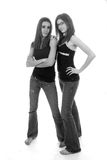 Black and white beauties. Pretty slender teenage girls in tight denim and bare feet Royalty Free Stock Photography