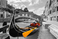 Black and white of a beautiful canal in Venice with selective color on the gondola. Black and white photo of a gondola anchored along a canal in the city of Stock Photography