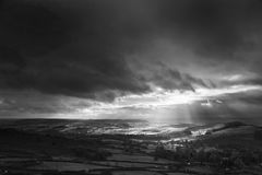 Black and white beautiful sunbeams over Big Moor in the Peak Dis. Stunning black and white sunbeams over Big Moor in the Peak District landscape in Autumn stock photo