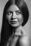 Black and white beauty with freckles. Beautiful fashion model with freckles, makeup and dark hairstyle Royalty Free Stock Image