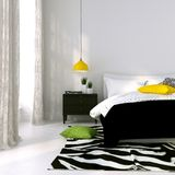 Black and white bed and a yellow lamp Royalty Free Stock Photography
