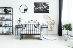Metal furniture and tree plant. Black and white bedroom with metal furniture and tree plant standing by a white window with black drapes Stock Photo