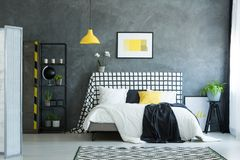 Bed against dark textured wall. Black and white bedsheets on king-size bed against dark textured wall in bedroom with plant in blue pot on black stool Stock Photography