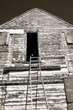 Black and White) Bent ladder reaches to a granary door Royalty Free Stock Image