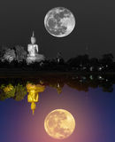 Black and white big buddha statue with super moon and colorful big golden buddha statue reflection Stock Photography