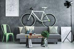 Black and white bike. Black and white sports bike standing on the couch with cushions next to studio lamp Stock Images