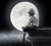 Black&white-Bild eines kleinen Jungen, der auf dem Dach sitzt stockbild