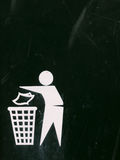 A black and white bin sign with texture scratches and dents and. Marks and fade, interesting symbol of person putting rubbish into a bin to keep the place clean Royalty Free Stock Image