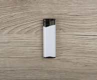 Black-and-white blank gas lighter on a wooden background. Royalty Free Stock Photos