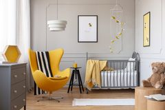 Black and white blanket on yellow egg chair in grey baby bedroom with black wooden stool with mug and grey crib with cozy blanket