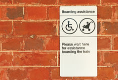 Black and white Boarding Assistance sign on red brick wall Royalty Free Stock Image