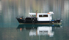 Black and white boat on lake with reflection Royalty Free Stock Images