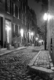 Black and white boston. Black and white image of an old 19th Century cobble stone road in Boston Massachusetts, lit only by the gas lamps revealing the shuttered Stock Photos