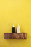 Black and white bottles container on wooden shelf in toilet with yellow wall. Black and white bottles container on wood shelf in toilet with yellow wall Royalty Free Stock Photography